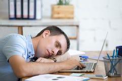 Giovane che dorme sulla scrivania Fotografia Stock