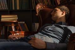 Giovane che dorme sulla sedia che tiene un libro Fotografie Stock Libere da Diritti