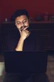 Giovane che esamina computer portatile e che pensa nella stanza scura fotografie stock libere da diritti
