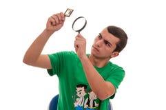 Giovane che esamina con una lente d'ingrandimento una pellicola fotografica Fotografia Stock Libera da Diritti