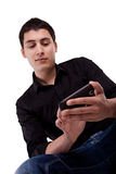 Giovane che esamina il suo telefono astuto. Immagini Stock