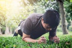 Giovane che esercita forma fisica di allenamento che fa tavolato fuori sul g Immagini Stock