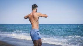 Giovane che fa allungando esercizio sulla spiaggia Fotografie Stock Libere da Diritti