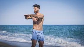 Giovane che fa allungando esercizio sulla spiaggia Fotografia Stock