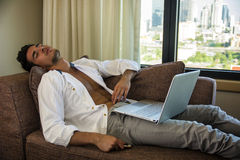 Giovane che fa compito sul computer portatile in camera da letto Fotografie Stock Libere da Diritti