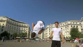 Giovane che fa i salti mortali nella via video d archivio