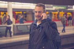 Giovane che fa una chiamata con lo smartphone alla stazione della metropolitana Immagine Stock