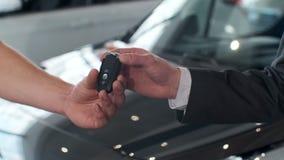 Giovane che fornisce le chiavi dell'automobile al compratore Uomini che stringono le mani nel bello concessionario auto su fondo  video d archivio