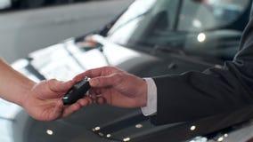 Giovane che fornisce le chiavi dell'automobile al compratore Uomini che stringono le mani nel bello concessionario auto su fondo  stock footage