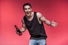 Giovane che gesturing con la bottiglia di birra e che sorride alla macchina fotografica Fotografie Stock