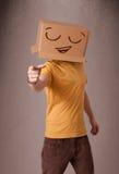 Giovane che gesturing con una scatola di cartone sulla sua testa con lo smiley Immagine Stock