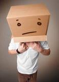 Giovane che gesturing con una scatola di cartone sulla sua testa con straig Fotografia Stock Libera da Diritti