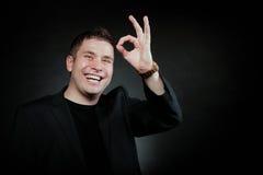Giovane che gesturing il segno della mano di approvazione di approvazione Immagine Stock