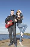 Giovane che gioca chitarra con la donna che sta ballando immagine stock