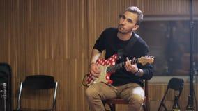 Giovane che gioca chitarra elettrica rossa e bianca stock footage
