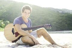 Giovane che gioca chitarra sulla spiaggia immagine stock libera da diritti