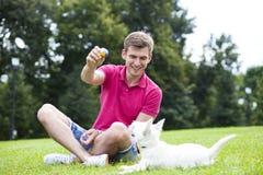 Giovane che gioca con il suo cane nel parco immagini stock libere da diritti