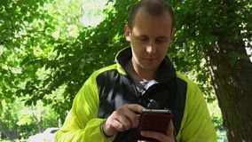 Giovane che gioca il telefono, nei precedenti degli alberi verdi video d archivio