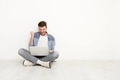 Giovane che gioca sul computer portatile che si siede sul pavimento Fotografie Stock Libere da Diritti