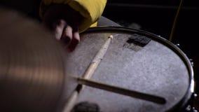 Giovane che gioca un insieme del tamburo in una stanza scura 4K Clous su Primo piano delle mani del batterista Sparato nello stil stock footage
