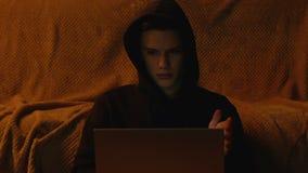 Giovane che gioca video gioco sul computer portatile alla notte, problemi di tecnica, fine su video d archivio