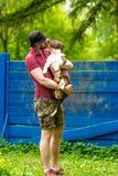 Giovane che gode di un giorno soleggiato nel parco con il suo cane Il proprietario dell'animale domestico che riceve un bacio lec fotografia stock