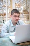 Giovane che guarda in computer portatile Fotografia Stock Libera da Diritti