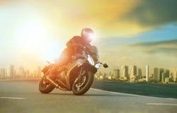 Giovane che guida grande motociclo che si appoggia curva tagliente con il urba fotografie stock libere da diritti