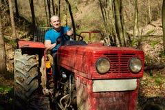 Giovane che guida un trattore in una foresta Fotografia Stock