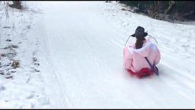 Giovane che guida una slitta giù la collina di un pendio dello sci, degli sport invernali e dei giocattoli di divertimento, dell' stock footage