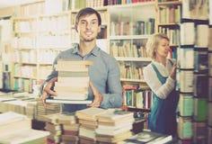 Giovane che ha mucchio del libro in mani Fotografia Stock Libera da Diritti