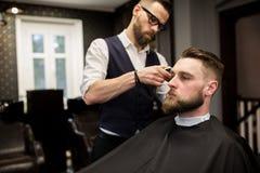 Giovane che ha taglio di capelli nel salone di capelli fotografie stock libere da diritti