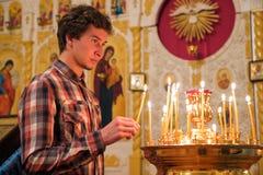Giovane che illumina una candela nella chiesa. fotografia stock