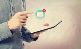 Giovane che indica ad un'icona del email sopra una compressa illustrazione di stock