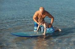 Giovane che insegna praticando il surfing suo figlio nell'oceano in un giorno soleggiato Fotografie Stock Libere da Diritti