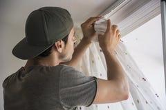 Giovane che installa le tende sopra la finestra fotografia stock libera da diritti