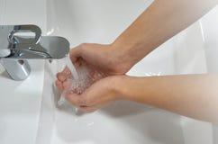 Giovane che lava le mani sotto il rubinetto con acqua immagine fotografia stock
