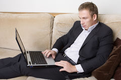 Giovane che lavora ad un computer portatile Immagini Stock