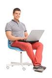 Giovane che lavora ad un computer portatile messo su una sedia Immagini Stock