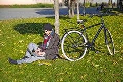 Giovane che lavora ad un computer portatile in un parco di autunno. Immagini Stock