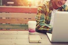 Giovane che lavora al computer in caffè della via, free lance che fanno il suo lavoro all'aperto Immagine Stock