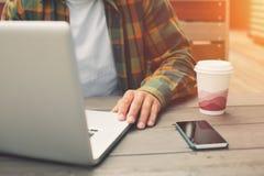 Giovane che lavora al computer in caffè della via, free lance che fanno il suo lavoro all'aperto Fotografia Stock