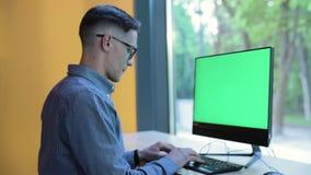 Giovane che lavora al computer con lo schermo verde all'interno archivi video