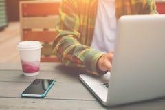 Giovane che lavora al computer e che si siede in caffè della via, free lance che fanno il suo lavoro all'aperto Fotografia Stock Libera da Diritti