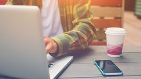Giovane che lavora al computer e che si siede nel caffè della via, nelle free lance e nel suo posto di lavoro Immagine Stock Libera da Diritti
