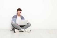 Giovane che lavora al computer portatile che si siede sul pavimento Fotografie Stock