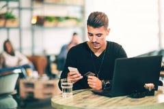 Giovane che lavora al computer portatile mentre sedendosi al caffè Immagine Stock Libera da Diritti