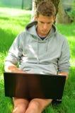 Giovane che lavora al suo computer portatile sotto l'albero Fotografia Stock Libera da Diritti