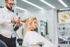 Giovane che lavora allo studio del parrucchiere Immagini Stock Libere da Diritti