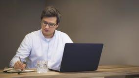Giovane che lavora con il computer portatile che annota informazioni in taccuino video d archivio